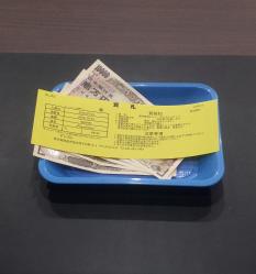 トレーに乗ったお金と質札